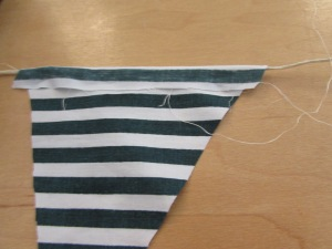 Carefully fold the flag over your twine (cut twine to desired length prior).
