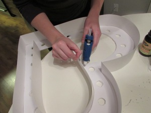 Using the glue gun, attach the strips.